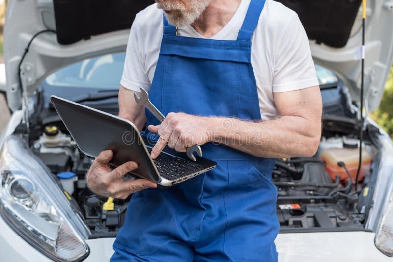 Mecánico que usa el ordenador portátil para comprobar el motor de coche fotos de archivo