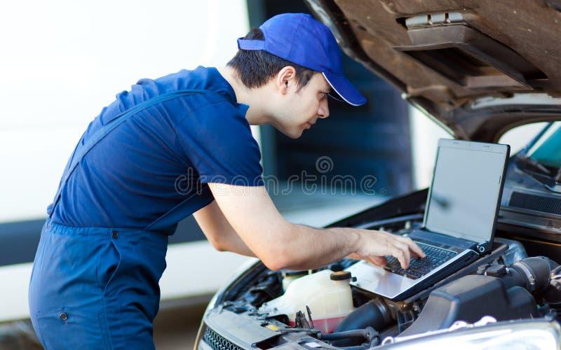 Mecánico que usa un ordenador portátil para comprobar un motor de coche imagenes de archivo