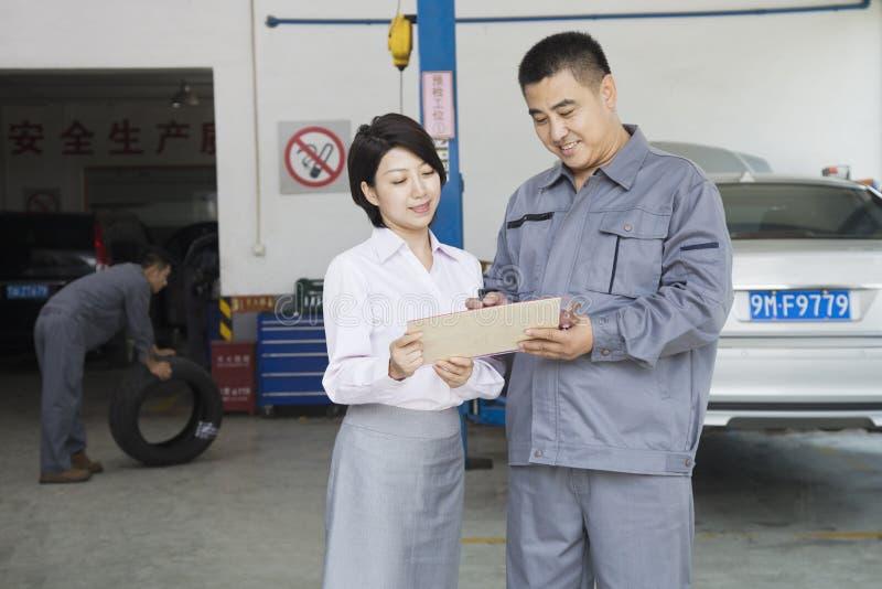 Mecánico sonriente Explaining del garaje al cliente, mostrándole el Bill foto de archivo