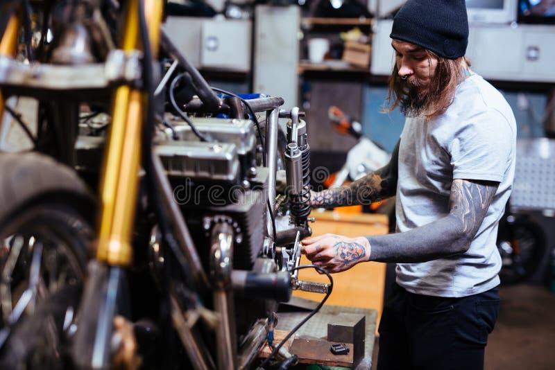 Mecánico tatuado Assembling Motorcycle en garaje fotografía de archivo