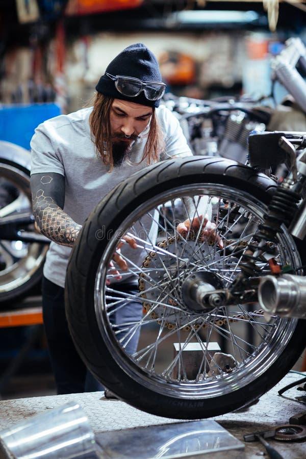 Mecánico tatuado Assembling Motorcycle en garaje del taller fotos de archivo libres de regalías