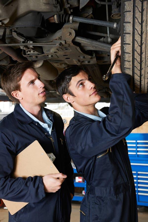 Mecánico And Trainee Working debajo del coche imagenes de archivo