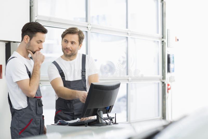 Mecánicos de automóvil de sexo masculino que conversan en el taller de reparaciones fotos de archivo