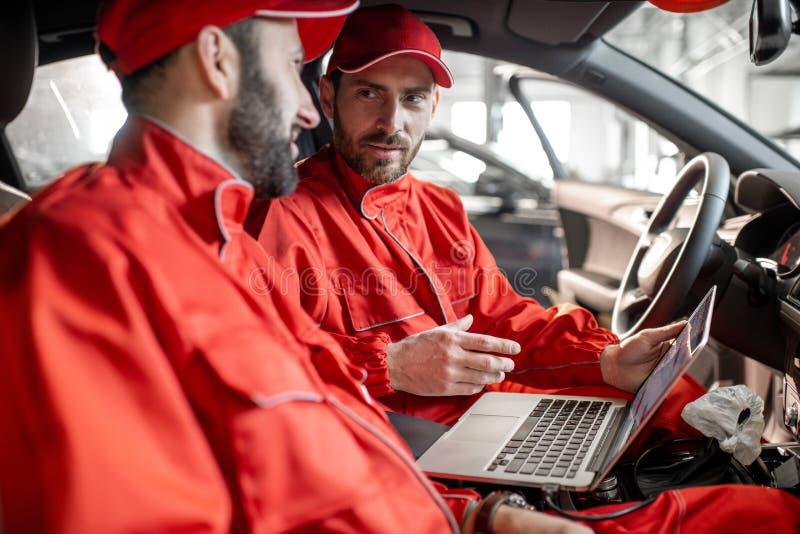 Mecánicos de automóviles que diagnostican el coche con el ordenador imagen de archivo libre de regalías