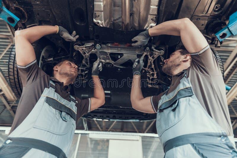 Mecánicos de automóviles que trabajan por debajo el coche levantado fotografía de archivo