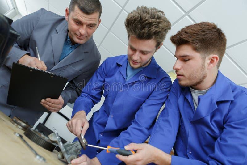 Mecánicos del aprendiz que trabajan en taller de reparaciones auto foto de archivo
