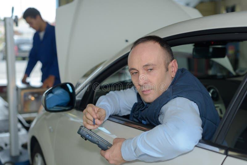 Mecánicos que intentan encontrar problema del coche imagen de archivo