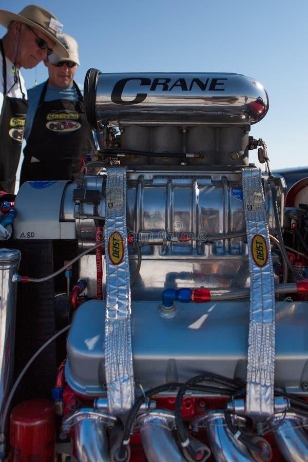 Mecánicos que miran un motor del coche de competición durante el mundo del Spe imagen de archivo