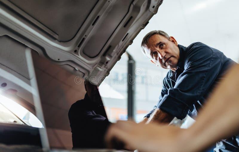 Mecánicos que trabajan en un coche quebrado en garaje fotos de archivo