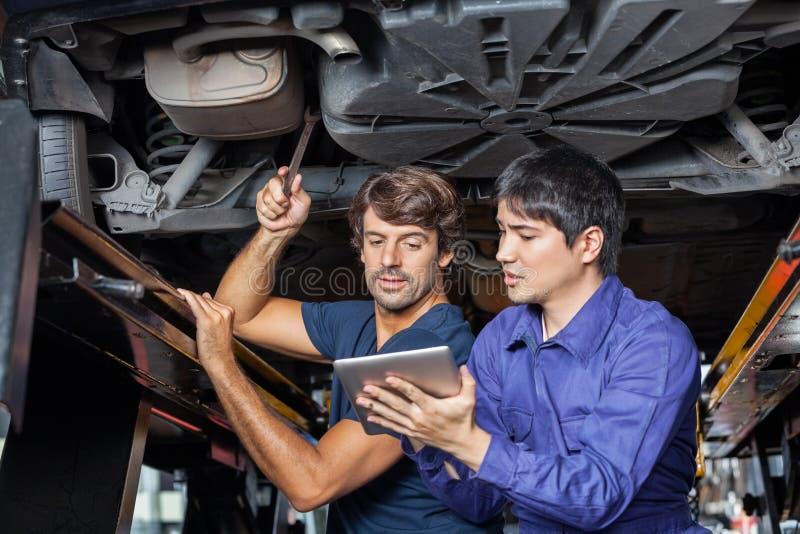 Mecánicos que usan la tableta de Digitaces debajo del coche levantado foto de archivo