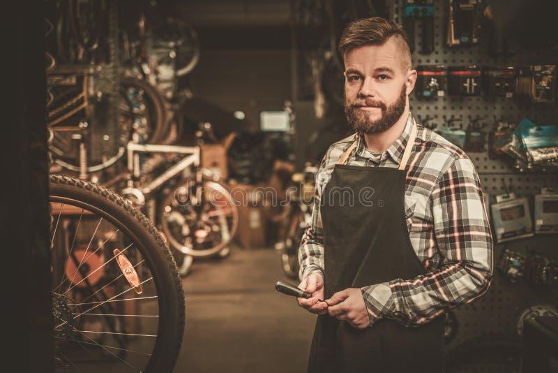 Mecânico à moda da bicicleta que faz seu trabalho profissional na oficina imagens de stock royalty free