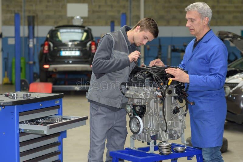 Mecânico In Auto Shop do aprendiz que trabalha no motor de automóveis fotografia de stock