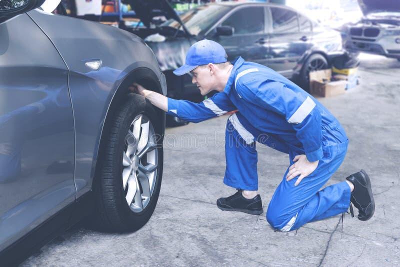 Mecânico caucasiano que verifica em um pneumático em uma oficina foto de stock royalty free