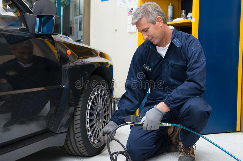 Mecânico Checking Tyre Pressure imagem de stock