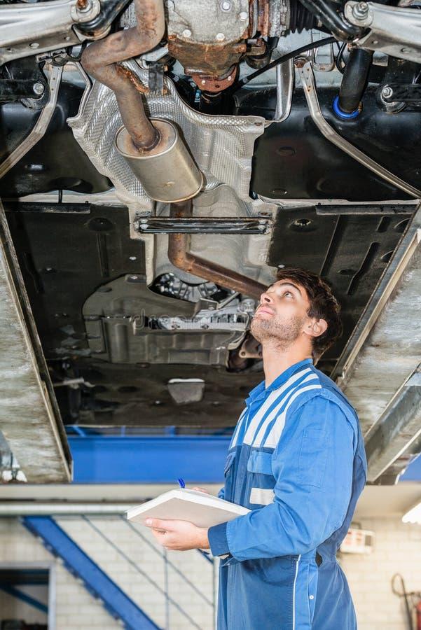 Mecânico With Clipboard Examining sob o carro na garagem fotos de stock royalty free