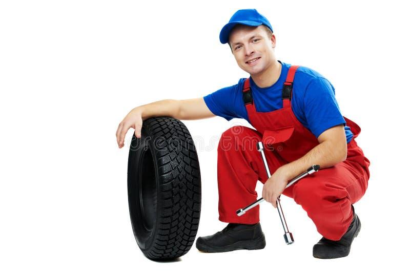 Mecânico de automóvel com pneu e chave inglesa de carro imagens de stock