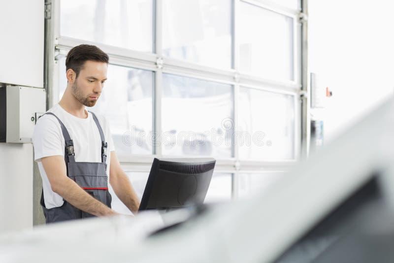 Mecânico de automóvel masculino novo que usa o computador na oficina de reparações foto de stock