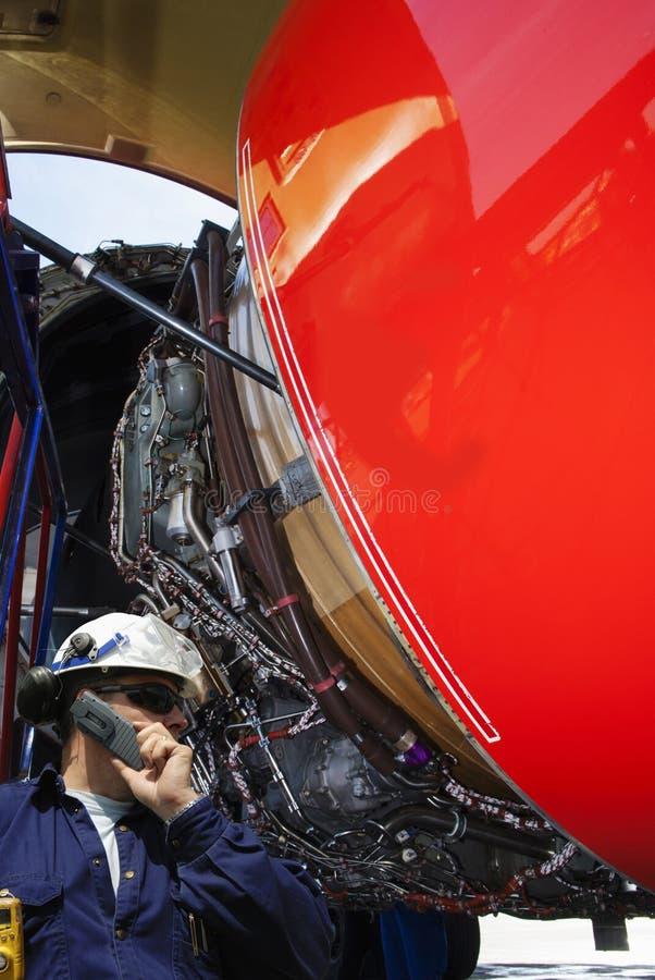 Mecânico de avião que inspeciona o motor de jato imagem de stock