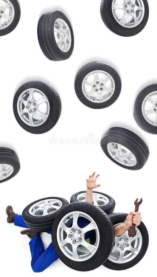 Mecânico de carro coberto com os pneus fotografia de stock