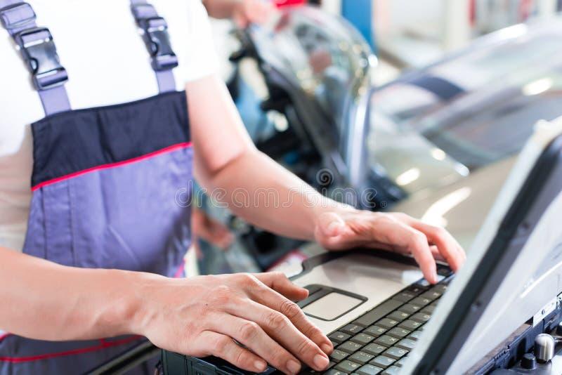 Mecânico de carro com a ferramenta do diagnóstico na auto oficina imagens de stock