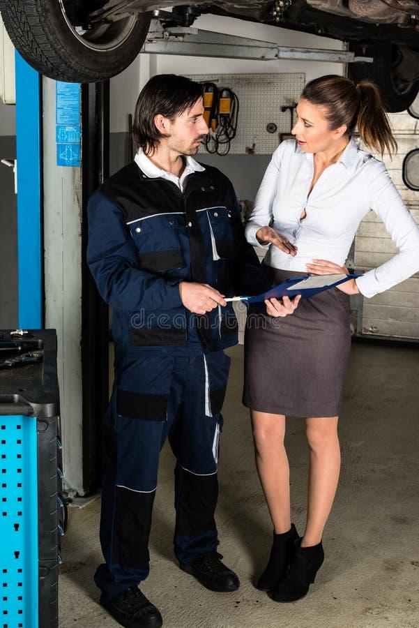 Mecânico de carro com o cliente fêmea irritado fotografia de stock