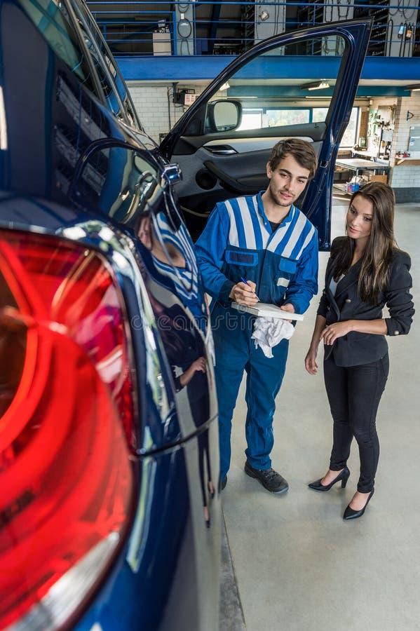 Mecânico de carro Preparing Checklist While que está com cliente fotografia de stock royalty free