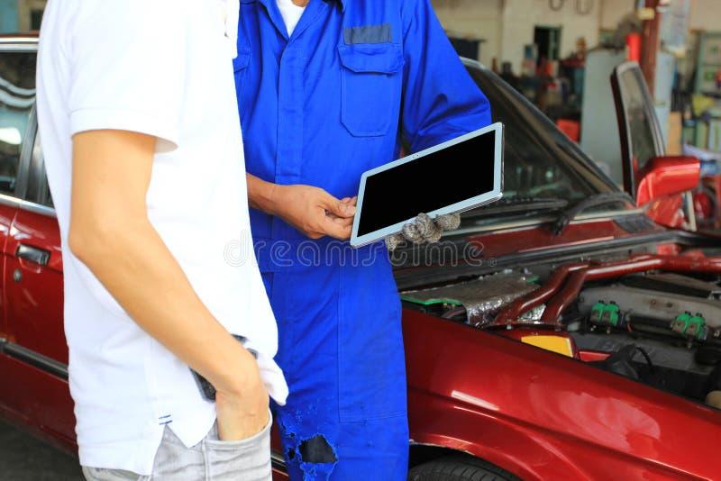 Mecânico de carro que mostra a tabuleta digital ao cliente o problema no serviço de reparação de automóveis foto de stock