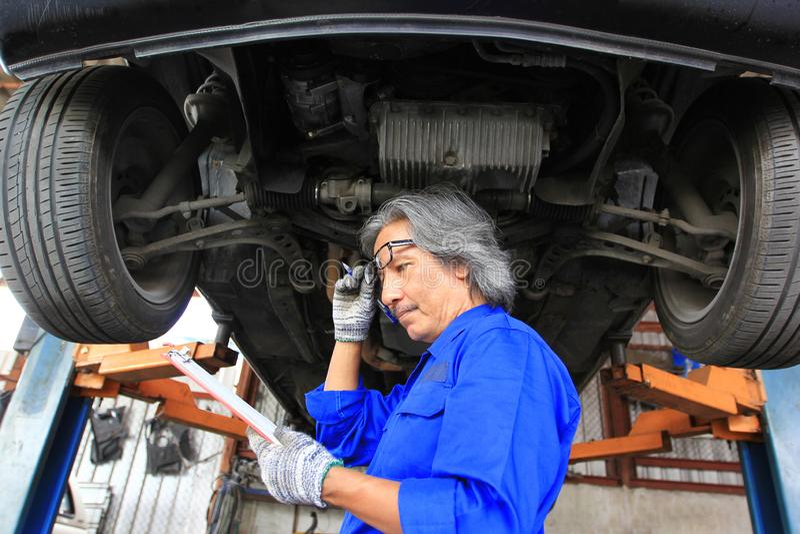Mecânico de carro que olha a prancheta com inspeção de dano no serviço de reparação de automóveis imagem de stock