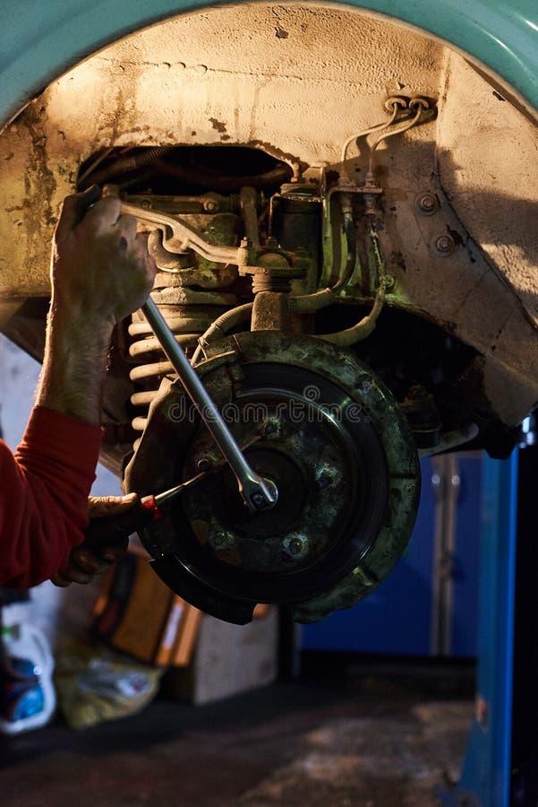 Mecânico de carro que repara o disco dos freios no carro, serviço de reparações interno imagem de stock royalty free
