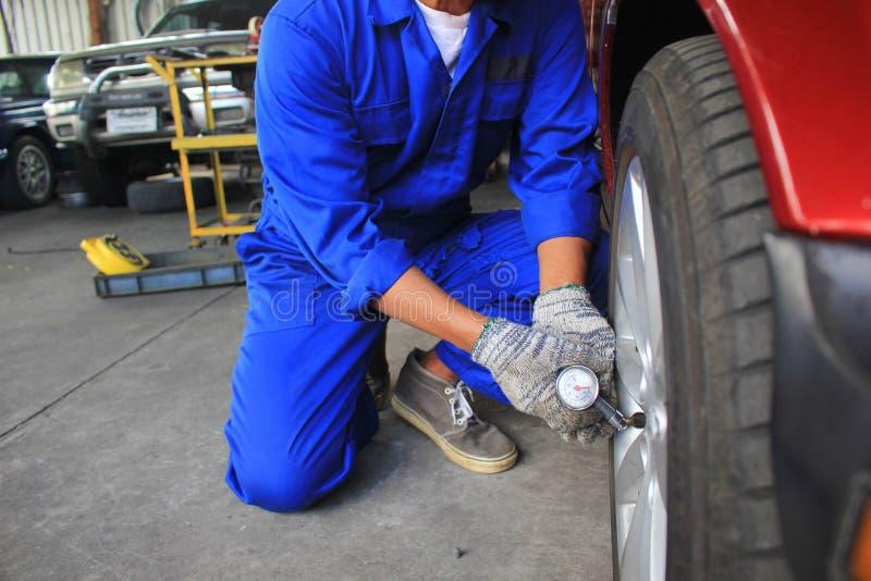 Mecânico de carro que verifica o calibre de pressão do ar para ver se há o carro no serviço de reparação de automóveis imagem de stock
