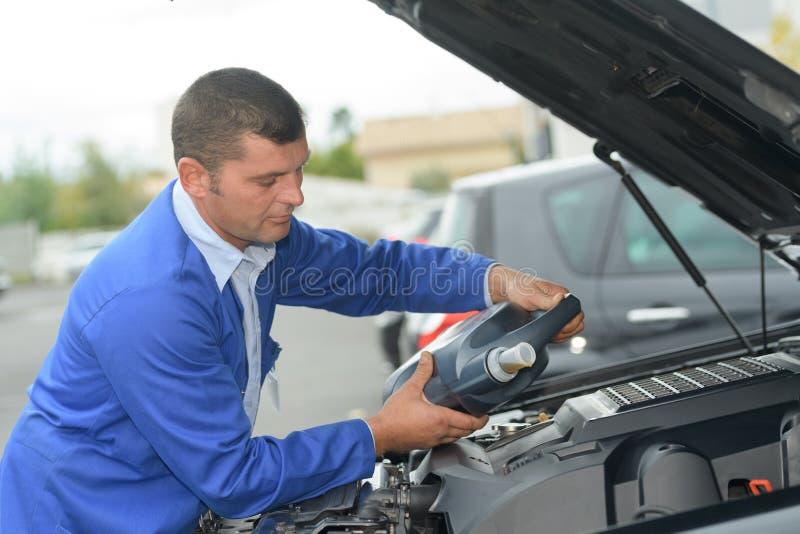 Mecânico de conservação que derrama o lubrificante novo do óleo no motor de automóveis fotos de stock royalty free