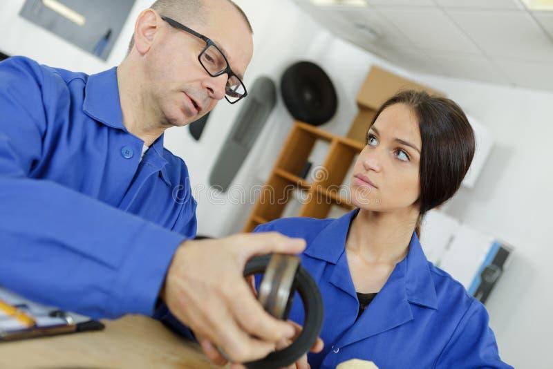 Mecânico e assistente fêmea que trabalham na loja de reparação de automóveis imagem de stock