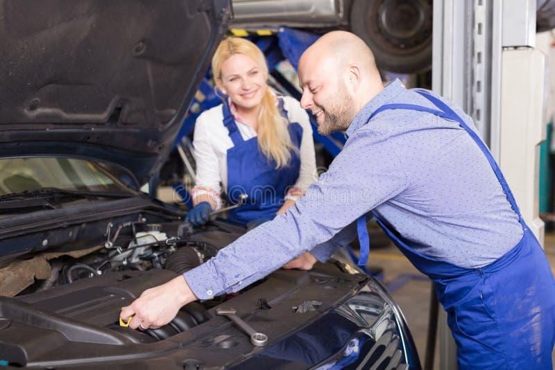 Mecânico e assistente que trabalham na loja de reparação de automóveis fotografia de stock