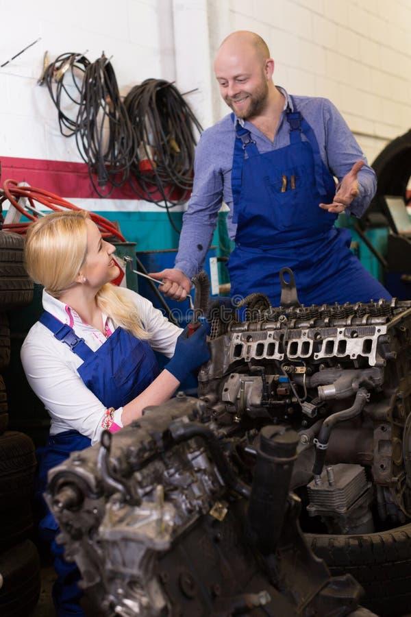 Mecânico e assistente que trabalham na loja de reparação de automóveis imagens de stock