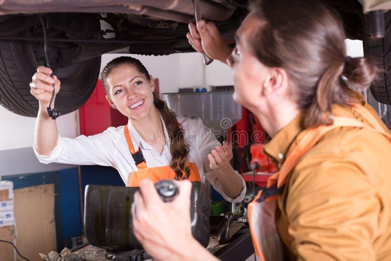 Mecânico e assistente que trabalham na oficina fotografia de stock royalty free