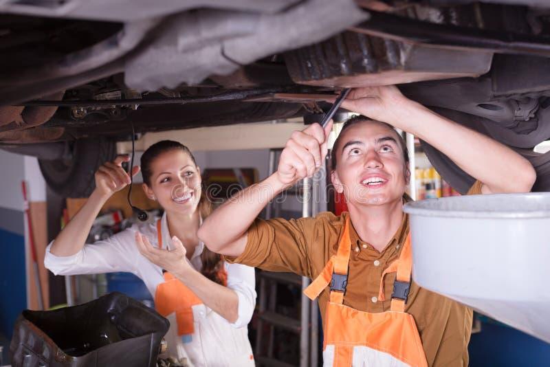 Mecânico e assistente que trabalham na oficina imagem de stock royalty free