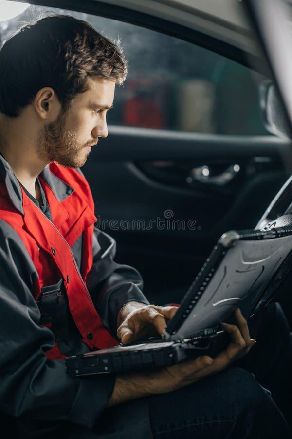 Mecânico Examining Car Engine com ajuda do portátil imagens de stock