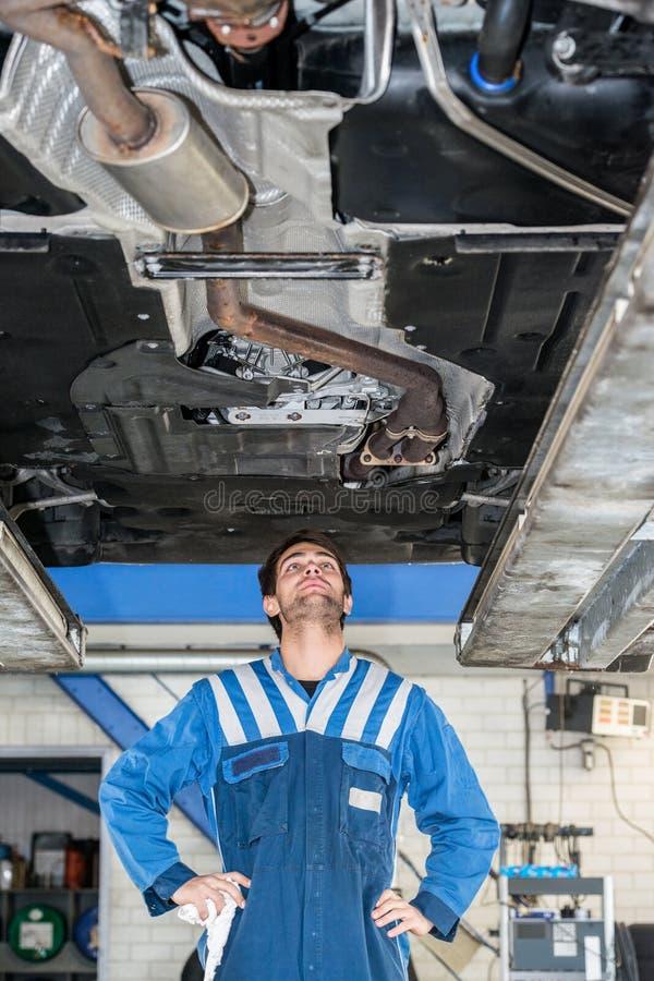 Mecânico Examining o estado de um sistema de exaustão sob o carro imagens de stock royalty free