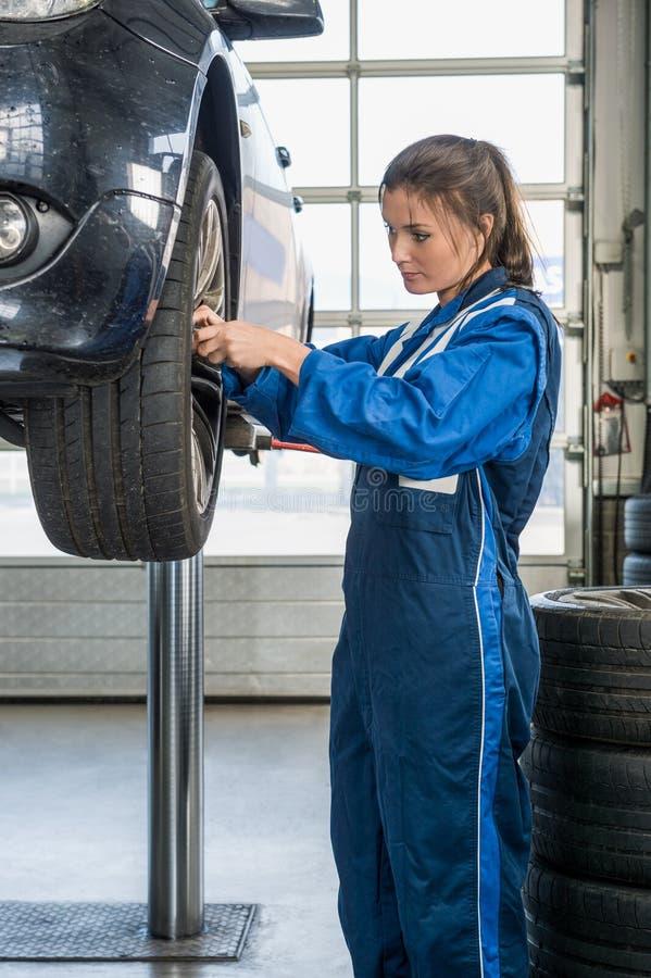 Mecânico fêmea Changing Car Tire no elevador na garagem fotografia de stock royalty free