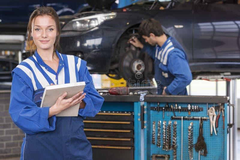 Mecânico fêmea na garagem do carro imagens de stock royalty free