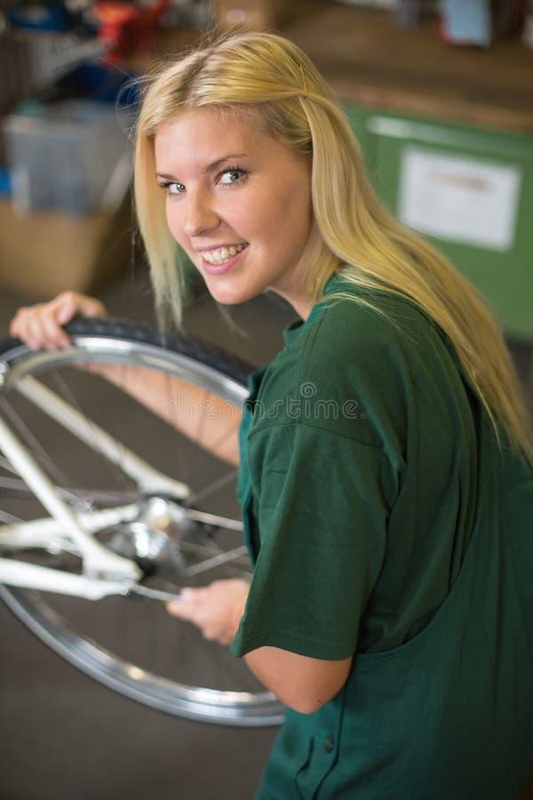 Mecânico fêmea na oficina que instala ou que repara uma bicicleta fotos de stock