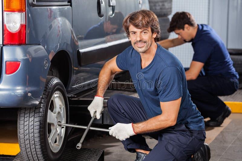 Mecânico Fixing Car Tire na loja de reparação de automóveis fotografia de stock royalty free