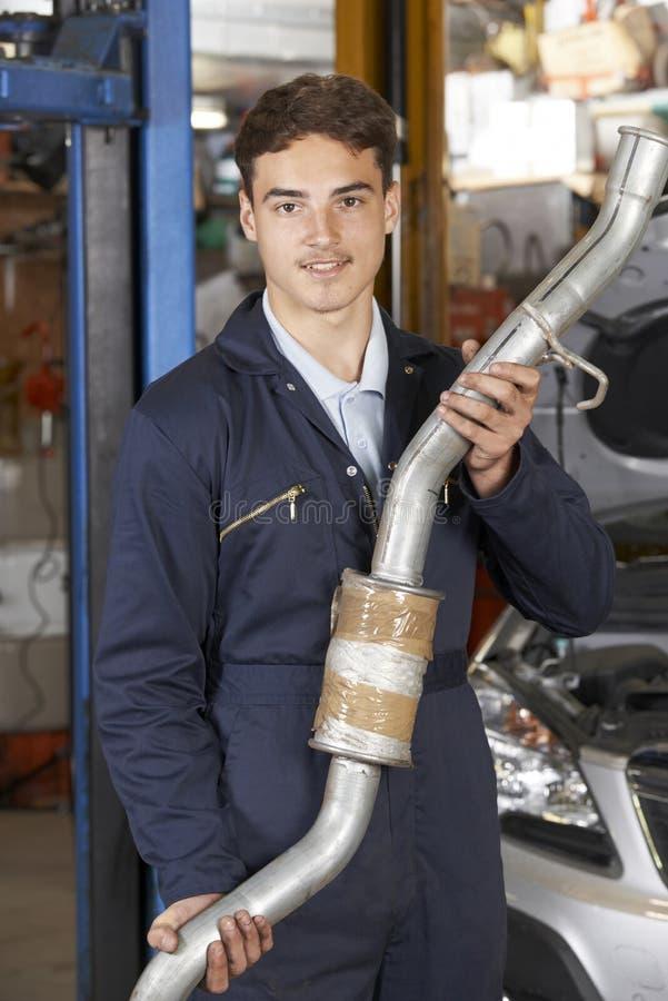 Mecânico Holding Exhaust Pipe do aprendiz na loja de reparação de automóveis fotografia de stock