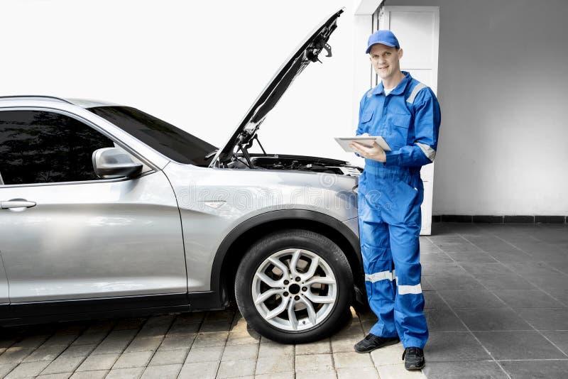 Mecânico masculino com carro e a tabuleta quebrados imagens de stock