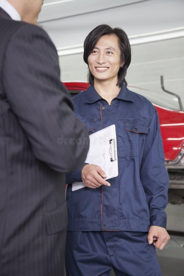Mecânico masculino com o cliente na loja de reparação de automóveis imagens de stock