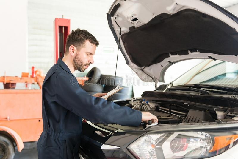 Mecânico masculino Examining Car Engine na oficina de reparações imagens de stock royalty free