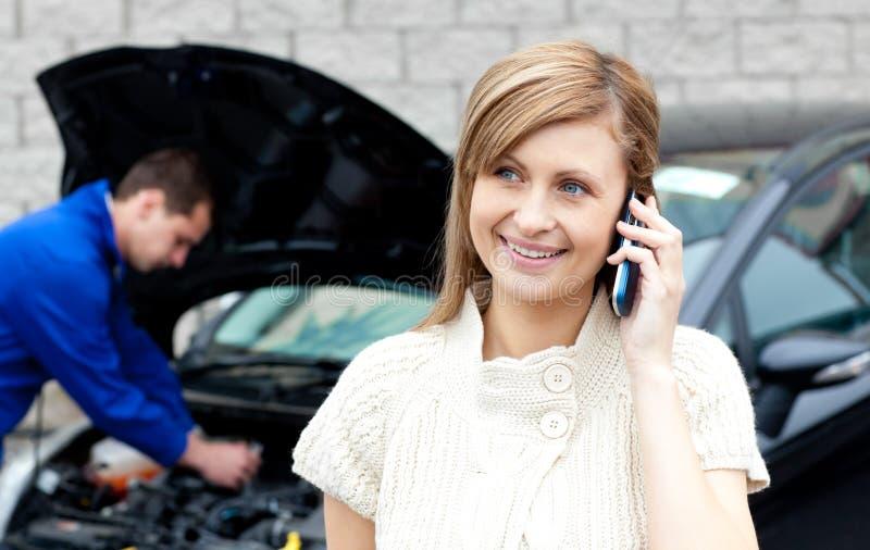 Mecânico masculino que repara o carro de uma mulher ocupada imagem de stock