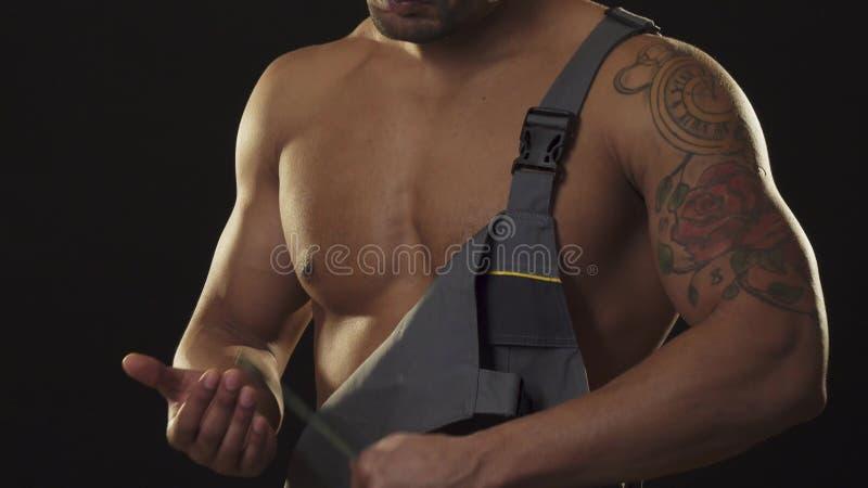 Mecânico muscular rasgado no workwear que olha a terra arrendada agressiva uma chave imagens de stock royalty free