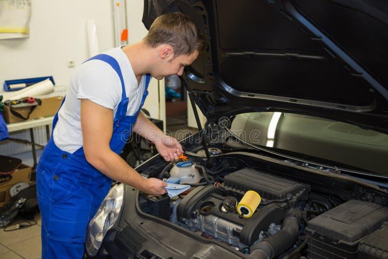 Mecânico na garagem que verifica o nível de óleo do motor em um carro imagens de stock royalty free