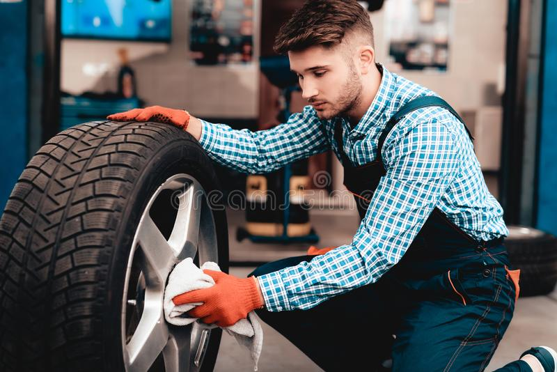 Mecânico novo Cleans Car Tire na estação do serviço fotos de stock royalty free